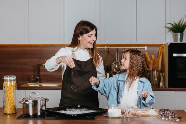 Imagem de uma mulher ensinando uma criança a preparar um alimento